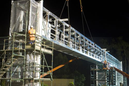 Workers in full PPE installing a gantry bridge over a motorway during the evening.  Scaffolding installed on both sides of the bridge. - Mining Photo Stock Library