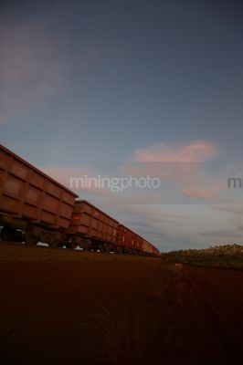 Iron ore train moving through the Pilbarra at dawn. generic photo of heavy rail. - Mining Photo Stock Library