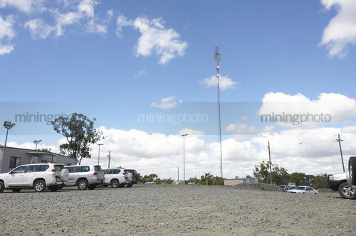 Communications tower in the car park of remote mine site. light vehicles parked up.  generic photo showing site office buildings. - Mining Photo Stock Library