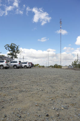 Communications tower in the car park of remote mine site. light vehicles parked up.  generic photo showing site office buildings.  vertical format photo. - Mining Photo Stock Library