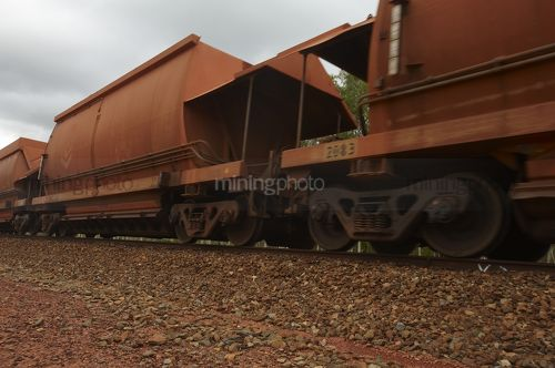 Close up photo of rail train  carriages moving at mine site. - Mining Photo Stock Library