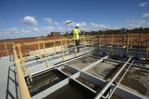 Mine site engineer testing water at treatment plant at remote mining site. - Mining Photo Stock Library