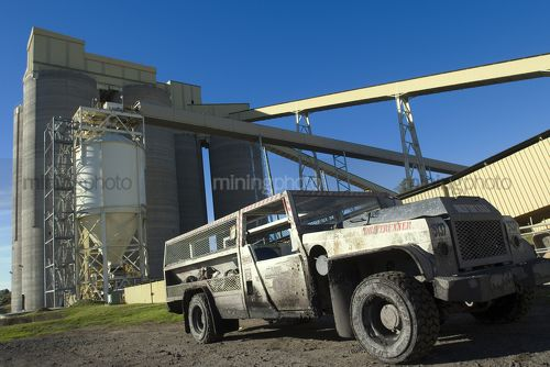 Drift runner underground coal vehicle  parked in front of storage tanks at mining site. - Mining Photo Stock Library