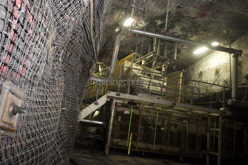 Close up photo of underground wall mesh in under ground coal mine.  machinery in the background. - Mining Photo Stock Library