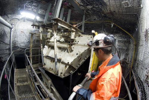 Underground coal mine engineer in full PPE observing machinery operating in under ground environment. - Mining Photo Stock Library