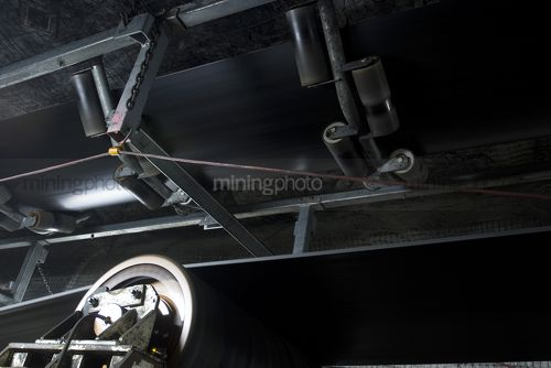 Close up photo of underground coal conveyor moving. - Mining Photo Stock Library