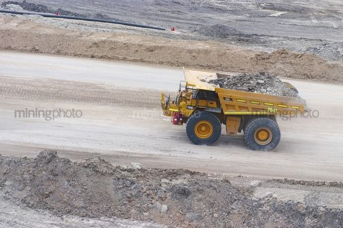 Aerial photo of haul truck moving with overburden on haul access road in open cut mine. - Mining Photo Stock Library