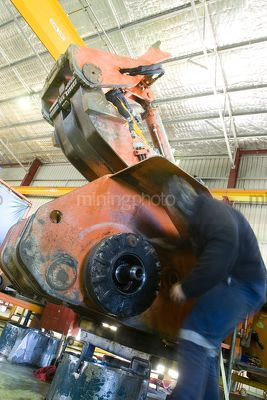 Industry shot of welder worker in full PPE moving around machinery in workshop. - Mining Photo Stock Library