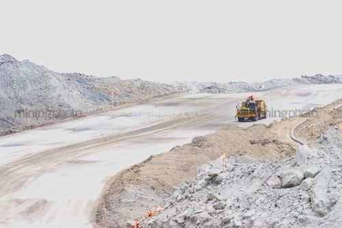 Earth scraper driving down haul access road in open cut mine site. - Mining Photo Stock Library