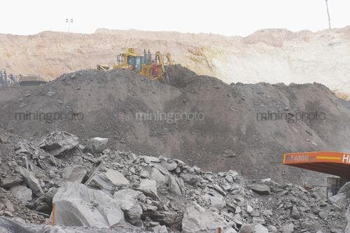 Dozer pushing overburden into a stockpile in open cut mine site.  very generic photo with room for copy. - Mining Photo Stock Library