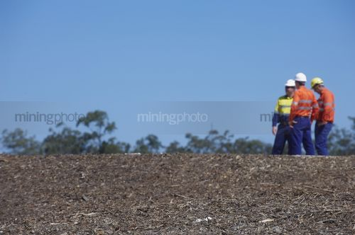 Three mine site workers in full PPE in discussion.  workers out of focus.   - Mining Photo Stock Library
