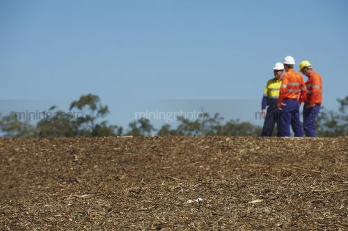Three mine site workers in full PPE in discussion.     - Mining Photo Stock Library