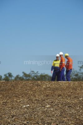 Three mine site workers in full PPE in discussion.    vertical shot. - Mining Photo Stock Library