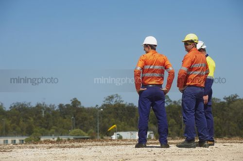 Three mine site workers in full PPE in discussion.  workers out of focus.  vertical shot. - Mining Photo Stock Library