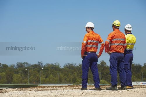 Three mine site workers in full PPE in discussion.  great generic photo for double page spread with room for copy. - Mining Photo Stock Library