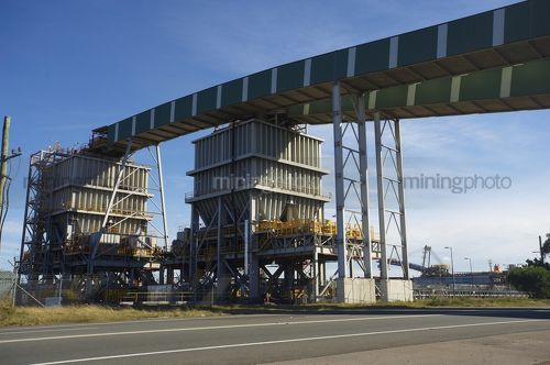 Enclosed coal conveyor crossing high over a road.  Ship loader in the background. - Mining Photo Stock Library
