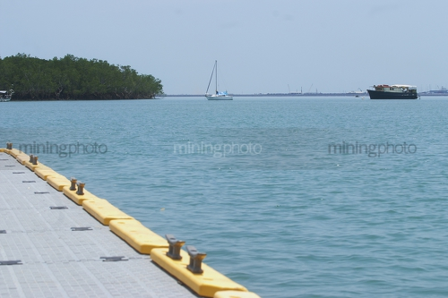 Looking over edge of a marine jetty with boats and mangroves on the horizon line. - Mining Photo Stock Library