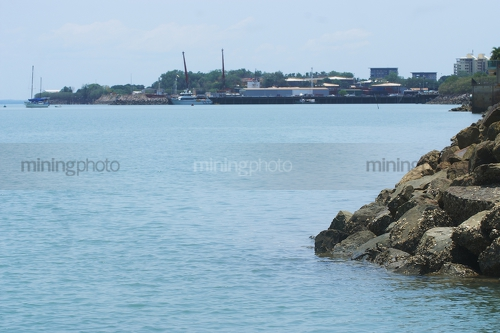 Photo looking over bay rock wall with town and wharves in the background. - Mining Photo Stock Library