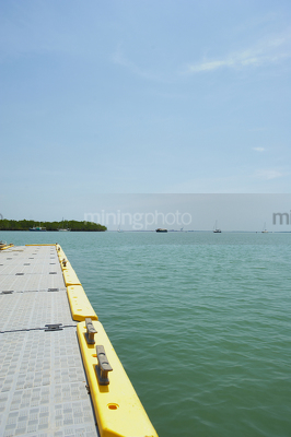 Looking over edge of a marine jetty with boats and mangroves on the horizon line.  vertical photo. - Mining Photo Stock Library