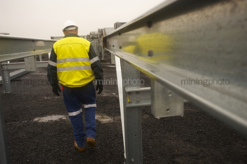 Construction manager in full yellow PPE walking amongst construction steel work.  steel is up close in foreground. - Mining Photo Stock Library