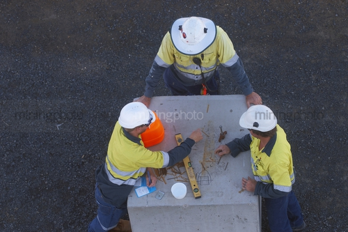Construction safety meeting.  aerial photo of 3 workers in full PPE including hard hats and long sleeves having a safety meeting. could be on a construction mine site.  faces cannot be seen.  workers are drawing out designs. - Mining Photo Stock Library