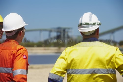 Two  mine site construction workers looking across a site.  large conveyor and stock pile in background. - Mining Photo Stock Library