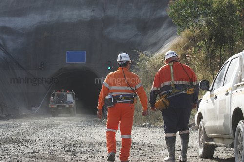 Photo of two underground workers walking towards the portal.  light vehicle 4wd driving down the mine site entrance. - Mining Photo Stock Library