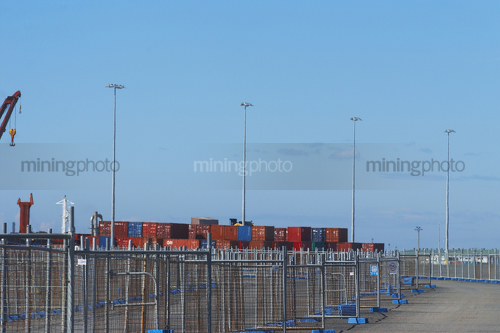 Photo of temporary fencing around ship at port.  shipping containers stacked on wharf.  bluer sky behind. - Mining Photo Stock Library