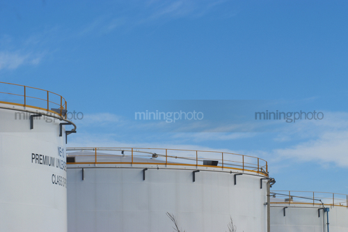 Photo of large fuel storage silos.  blue sky behind. - Mining Photo Stock Library