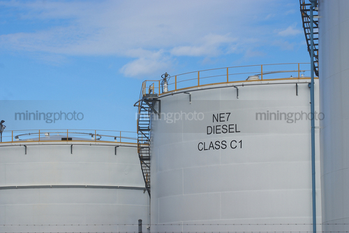Petrol storage towers with blue sky behind. - Mining Photo Stock Library