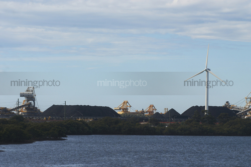 Great photo of a large wind generator and in the background is a reclaimer loading stockpiles of coal.  large dam in foreground. - Mining Photo Stock Library
