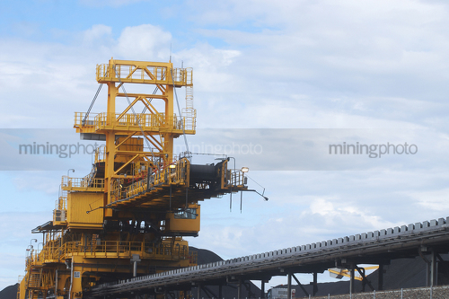 Shiploader loading coal with conveyor up close.  stockpiles of coal in background. - Mining Photo Stock Library