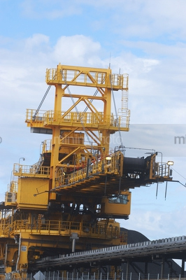 Shiploader loading coal with conveyor up close.  stockpiles of coal in background. vertical photo. - Mining Photo Stock Library