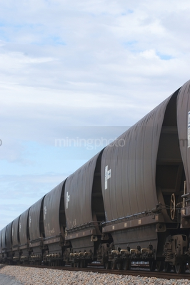 Vertical photo close up of heavy rail carriages for coal. - Mining Photo Stock Library