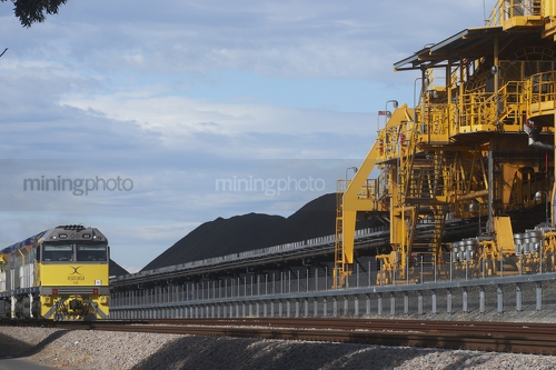 Coal train unloading at a stockpile with shiploader in foreground.  blue sky behind. - Mining Photo Stock Library