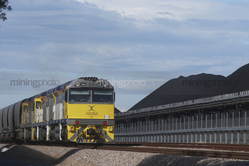 Coal train next to coal stockpiles. - Mining Photo Stock Library