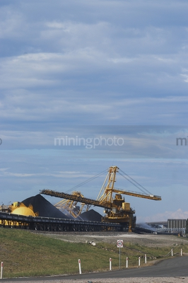 Photo of large shiploader and reclaimer working on coal stockpiles. light vehicle sealed road in foreground.  vertical photo. - Mining Photo Stock Library
