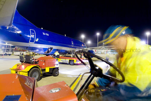 Workers in PPE involved in loading a large cargo plane with freight at night at airport. - Mining Photo Stock Library