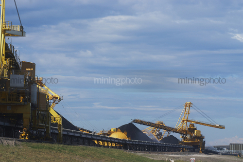 Photo of large shiploader and reclaimer working on coal stockpiles. light vehicle sealed road in foreground - Mining Photo Stock Library