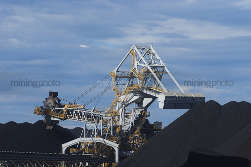 Close up photo of coal reclaimer next to stockpile.  blue sky behind. - Mining Photo Stock Library