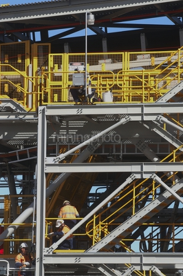 Mine site maintenance workers in full PPE working on coal conveyor.  vertical photo. - Mining Photo Stock Library
