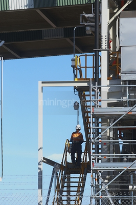 Mine worker in full PPE walking down stairs from conveyor site. - Mining Photo Stock Library