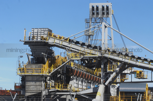 Close up photo of coal shiploader with blue sky behind. - Mining Photo Stock Library