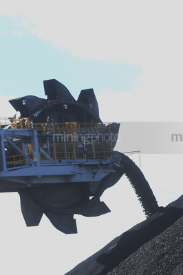 Close up silhouette of a coal loader stockpiling coal. - Mining Photo Stock Library