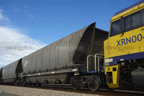 Close up photo of coal batgirl rail carriage directly behind a train engine. - Mining Photo Stock Library