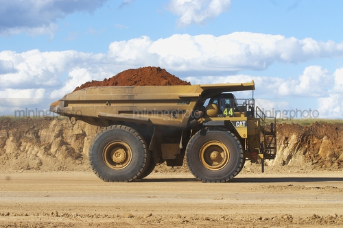 Side on photo of loaded 789 cat haul truck at open cut mine site. - Mining Photo Stock Library