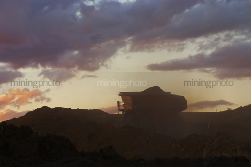 Silhouette of loaded haul truck on mine site.  photo taken at dusk. - Mining Photo Stock Library