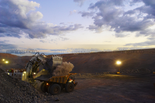 Great dusk photo of a digger loading a haul truck at open cut mine site.  lights are on. - Mining Photo Stock Library