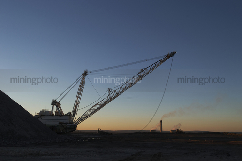 Dragline at open cut coal mine in afternoon light with coal fired power station stacks in background. - Mining Photo Stock Library