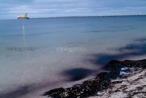 Ship and very long wharf in the distance being loaded. taken from the beach at water level.  - Mining Photo Stock Library